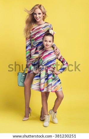 Fashion woman and a pretty little girl wearing the same colorful dresses. Photo of mother and daughter - stock photo