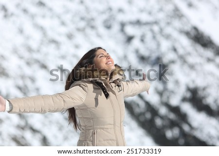 Fashion woman breathing fresh air in a snowy mountain in winter holidays - stock photo