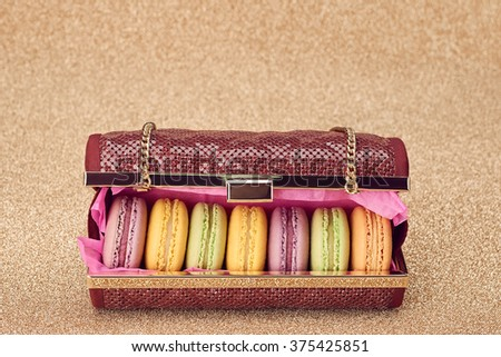 Fashion woman essentials set. Luxury handbag and Macarons. Ladies Fashionable glamor shiny clutch. Elegant fashion style. Creative party Outfit, fashion Accessories, golden background.Vintage