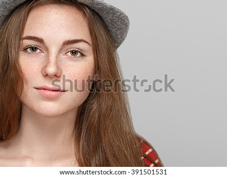 Fashion woman freckles portrait in hat on gray background - stock photo