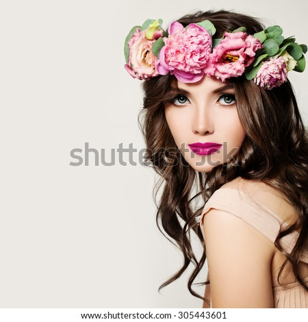 Fashion Woman. Girl with Makeup, Curly Hair and Pink Flowers