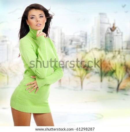 Fashion woman in autumn park holding yellow leaf - stock photo