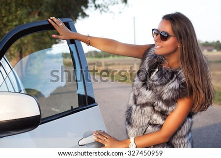 Fashion woman in fur vests, lady standing near car looking at sunset. Shopping inspiration. - stock photo