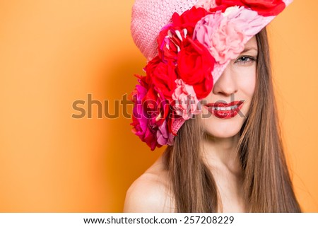 Fashion woman in hat over orange background, focus on face - stock photo