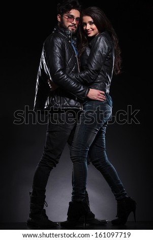 fashion woman in leather jacket is smiling while she embraces her boyfriend - stock photo
