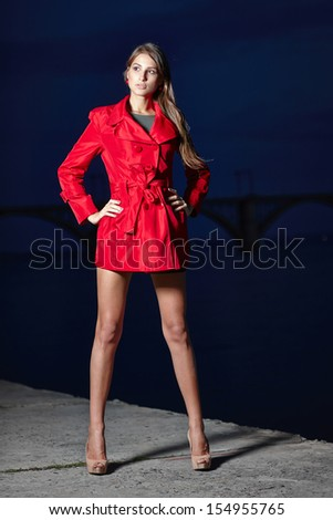 Fashion woman in red trench coat with hands on hips in full length posing against evening background outdoors - stock photo