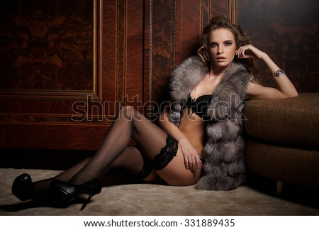 Fashion woman in underwear and fur coat sitting on the floor in antique room. - stock photo