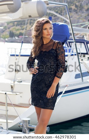 Fashion woman is standing near yacht
