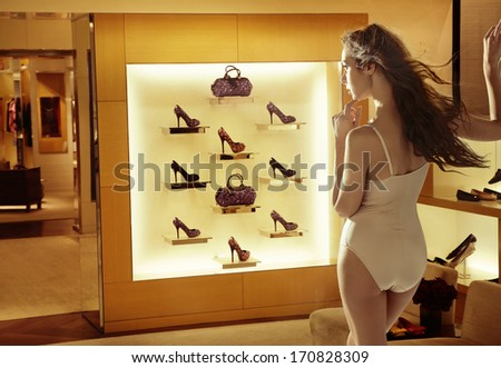 Fashion woman looking at high-heel shoes - stock photo