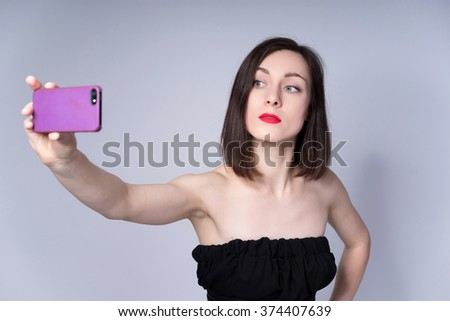 Fashion woman makes a selfie in a studio
