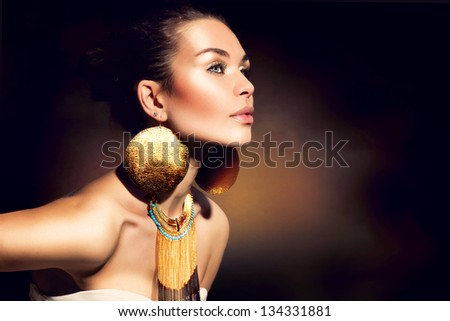 Fashion Woman Portrait. Golden Jewels. Trendy Makeup. Gold Jewellery. Accessories - stock photo