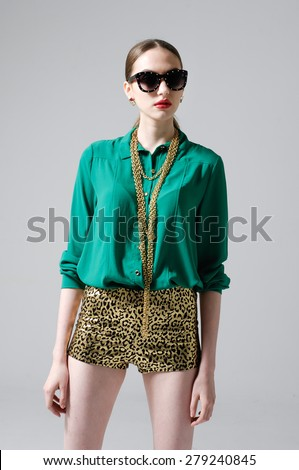 Fashion woman portrait wearing sunglasses and shorts posing on gray background - stock photo