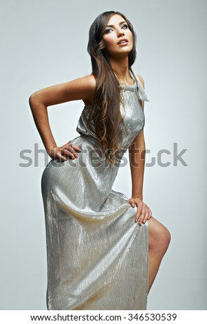 Fashion woman portrait. young model wearing silver evening dress. Studio isolated , gray background . Fashion model studio posing. - stock photo