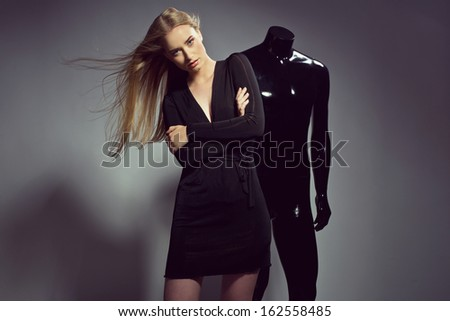 fashion woman posing with black mannequin