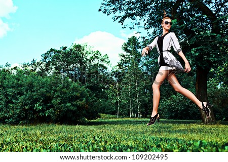 Fashion woman running in the summer park. - stock photo