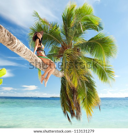 Fashion woman siting upon palm tree on the beach - stock photo