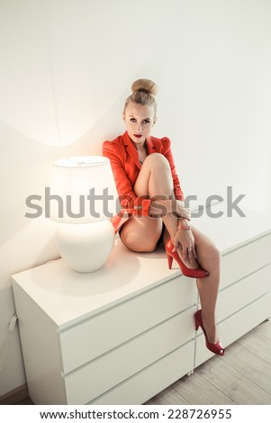 fashion woman sitting close to the lamp, unusual light effect - stock photo