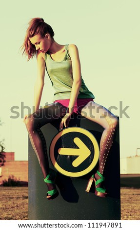 Fashion woman sitting on road sign indicating direction guide icon - arrow. Grunge, sepia style - stock photo