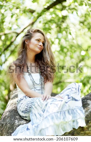 Fashion woman sitting on tree in spring park - stock photo