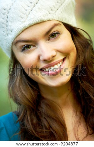 fashion woman smiling outdoors and wearing a hat - stock photo