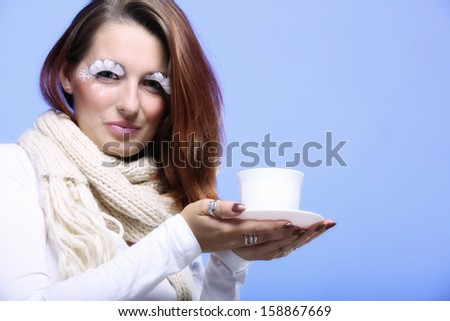 Fashion woman stylish winter makeup holding cup of hot drink beverage enjoying coffee time copy space blue background - stock photo