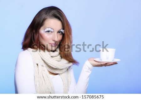 Fashion woman stylish winter makeup holding cup of hot drink beverge enjoying coffee time copyspace blue background