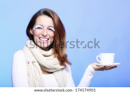 Fashion woman stylish winter makeup holding cup of hot drink beverge enjoying coffee time copyspace blue background - stock photo