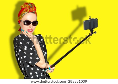 Fashion woman taking selfie over yellow background. focus on woman - stock photo
