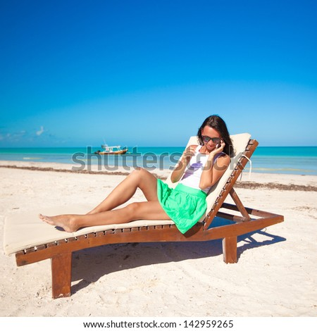 Fashion woman talking on the phone while sitting on a beach lounger - stock photo
