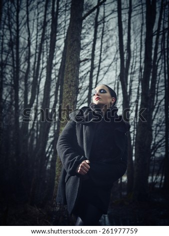 Fashion woman wearing a winter coat and she pose in a gloomy forest, cold rainy weather, cross processed full length image