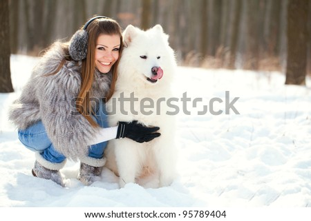fashion woman with dog samoyed in winter forest - stock photo