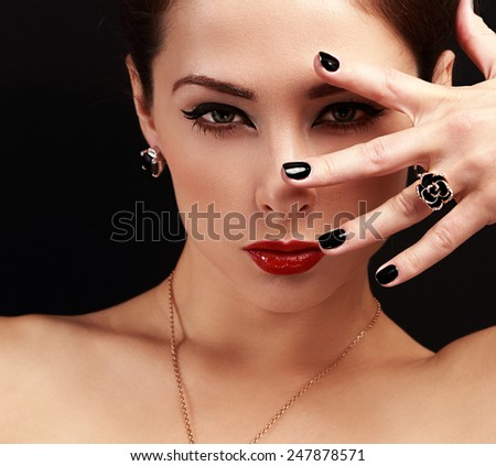 Fashion woman with jewelry accessory looking sexy with bright face makeup on black background. Closeup portrait - stock photo