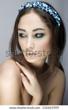 fashion woman with jewelry on light background with pearls headband - stock photo