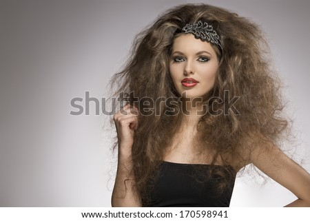 fashion woman with long brown curly hair style posing with pretty make-up and glitter accessory in the hair   - stock photo