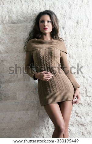 fashion woman with short sexy winter dress and perfect body. Posing with long hair and stylish make-up