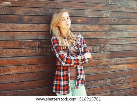 Fashion young blonde woman in checkered shirt over brown wooden background - stock photo