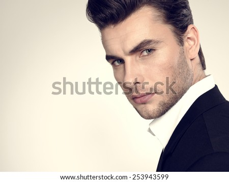 Fashion young businessman black suit casual  poses at studio