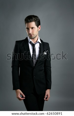 Fashion young businessman black suit casual tie on gray background - stock photo