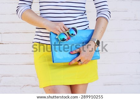 Fashion young girl hold blue clutch handbag and mirror sunglasses. Summer spring concept accessories - stock photo