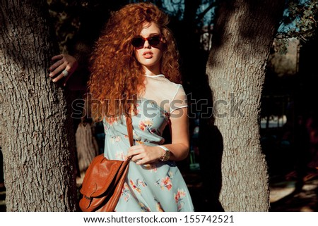 Fashion young girl near a tree . Horizontal shot in a park. outdoors  - stock photo