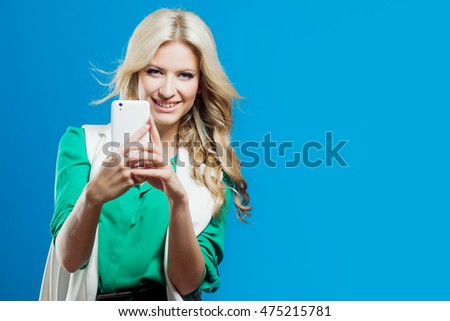 Fashion young girl taking picture, use the phone, blue background