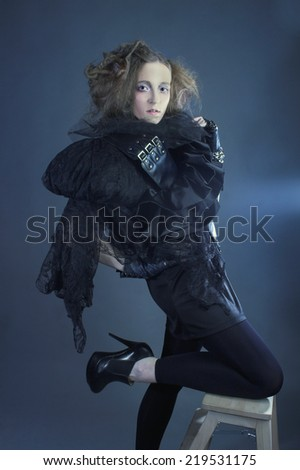 Fashion. Young lady in black and with artistic hairstyle.