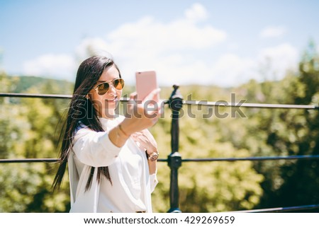 Fashion young lady taking a self portrait with her pink phone. Very shallow depth of field. - stock photo