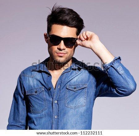 Fashion young man holding his fashionable sunglasses on gray background - stock photo