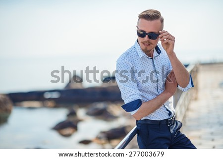 Fashion young man holding his fashionable sunglasses outdoor - stock photo