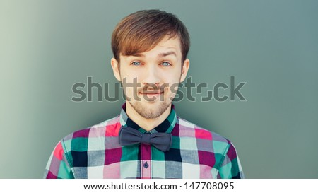 Fashion young man in shirt with bowtie looking at camera