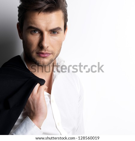 Fashion young man in white shirt holds the black jacket  over wall with contrast shadows - stock photo