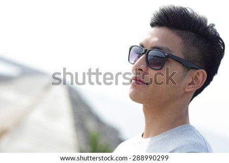 Fashion young man with his fashionable sunglasses, asian male - stock photo