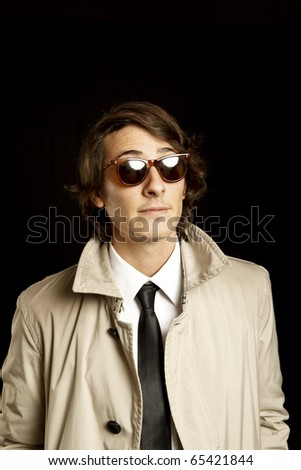 fashion young man with sunglasses and trenchcoat - stock photo