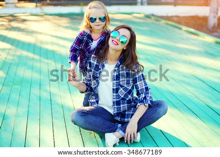 Fashion young mother and child daughter wearing a sunglasses and checkered shirt sitting in city